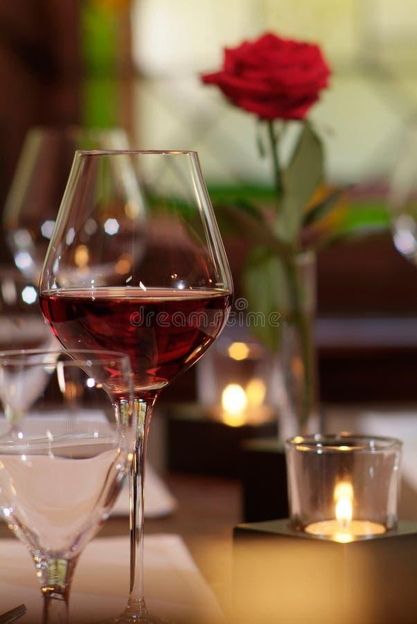 O vidro de vinho vermelho com vela e levantou-se fotos de stock royalty free