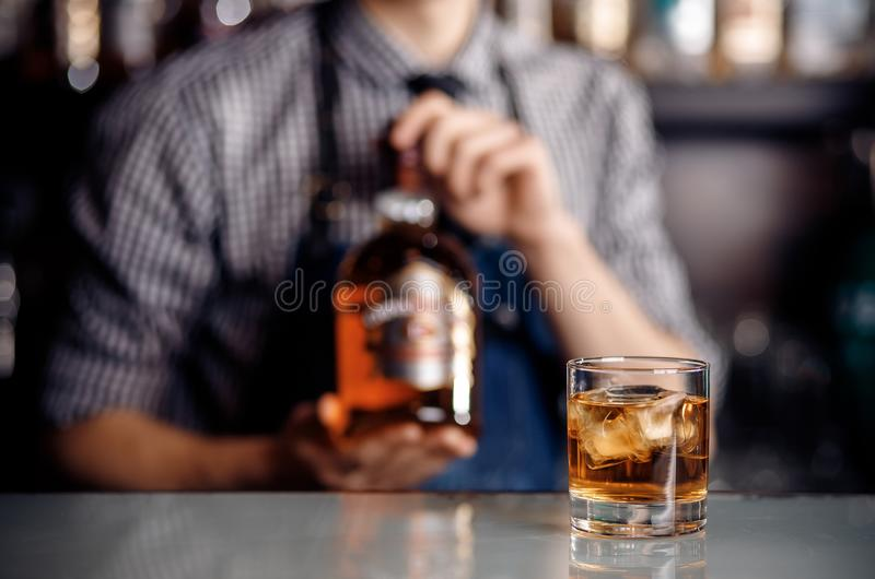 O vidro do álcool do uísque com gelo na barra, no empregado de bar do fundo guarda a garrafa M?scara escura imagens de stock