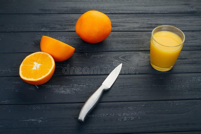 O vidro do suco de laranja na tabela de madeira, na madeira planta o fundo, na bebida fresca imagem de stock
