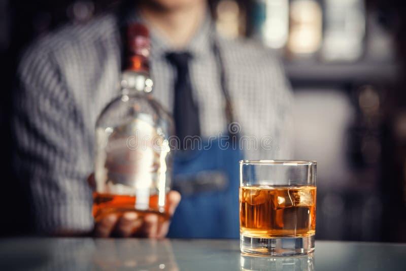 O vidro do uísque com gelo está na barra, barman pronto para encher o tiro fotos de stock