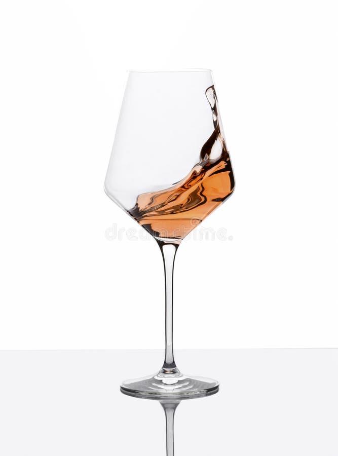 O vidro do vinho ambarino com espirra na tabela branca fotografia de stock