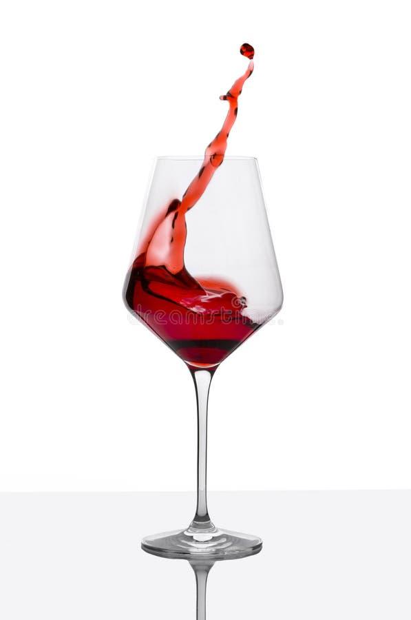 O vidro do vinho tinto com espirra na tabela branca foto de stock royalty free