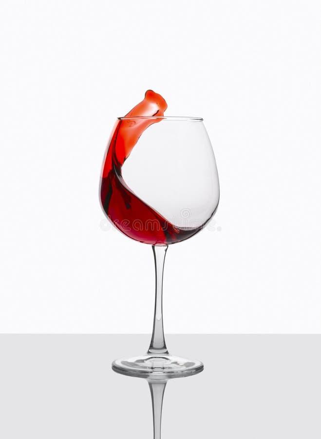 O vidro do vinho tinto com espirra na tabela branca imagem de stock royalty free