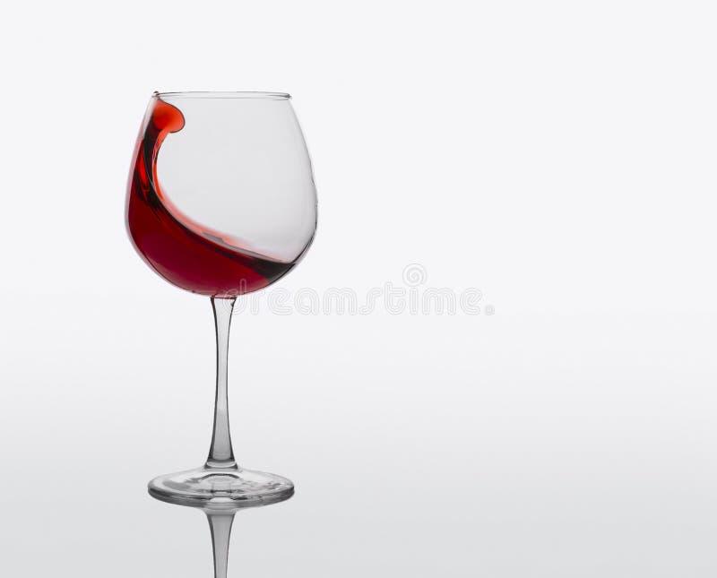 O vidro do vinho tinto com espirra no fundo branco imagens de stock