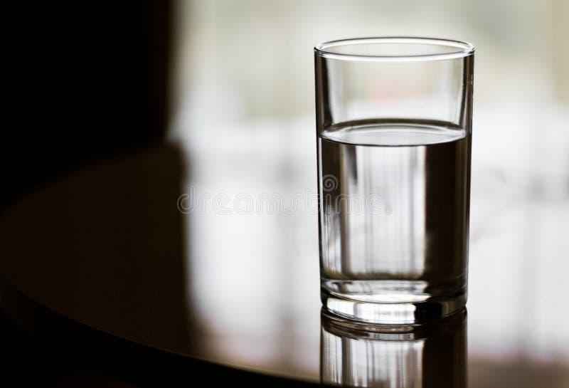 O vidro encheu-se com água na superfície reflexiva imagem de stock