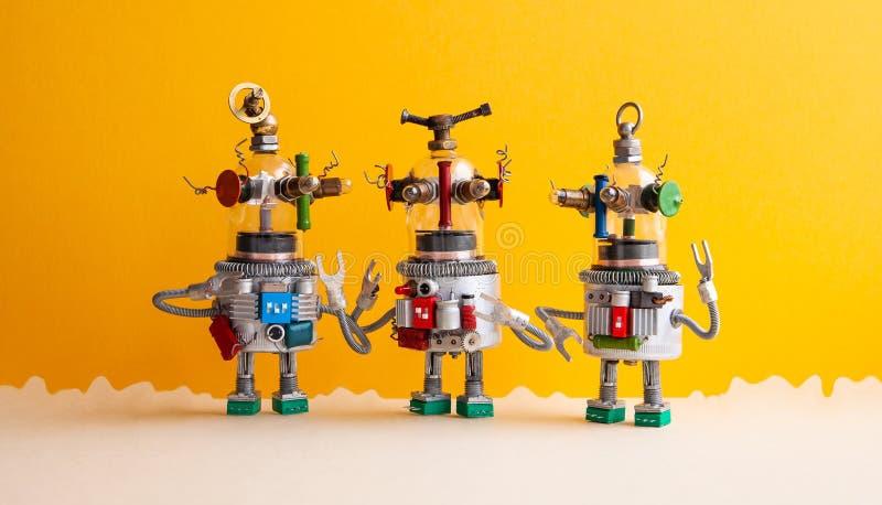 O vidro engraçado dirigiu robôs do UFO em uma paisagem fantástica Três robôs humanoid do brinquedo comunicam-se Fundo bege amarel fotografia de stock