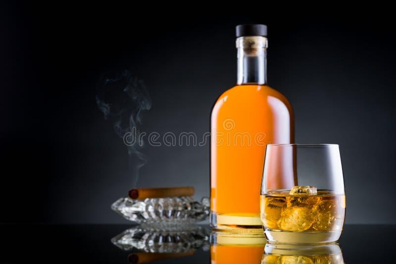 O vidro, a garrafa e o charuto do uísque no preto surgem fotografia de stock royalty free