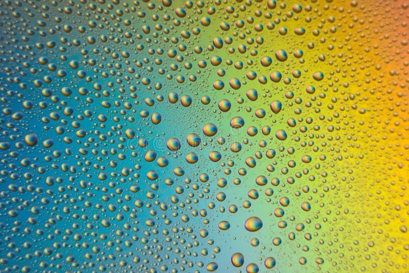 o vidro misted, close up das gotas no arco-íris coloriu o fundo foto de stock
