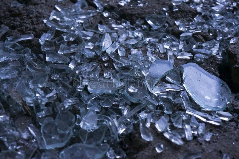 O vidro transparente quebrado, com um matiz azul, coberto com a poeira partes pequenas do brilho de vidro e vislumbra, refletindo imagens de stock