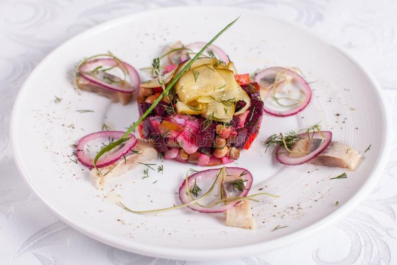 O vinagrete caseiro fresco da salada das beterrabas com arenques pesca em uma bacia branca Alimento tradicional do russo fotografia de stock