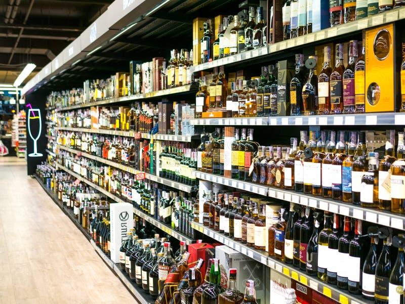 O vinho arquiva com os preços na exposição na loja em Kharkov, Uktaine Fileiras Defocused de garrafas do licor do vinho no th fotografia de stock