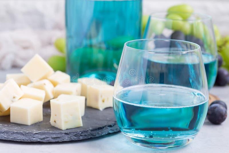 O vinho azul na moda do moscato em um vidro serviu com uma uva de placa de queijo, verde e vermelha no fundo, horizontal fotografia de stock