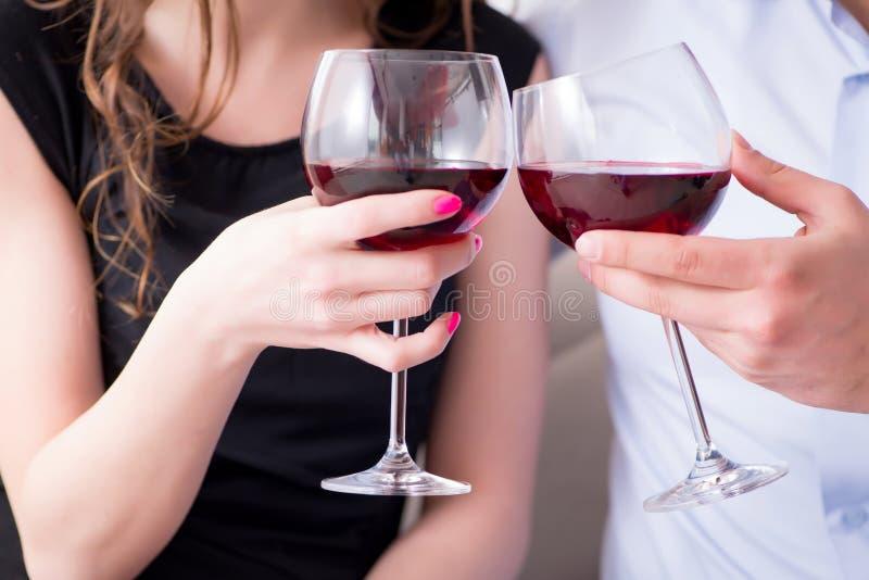 O vinho bebendo dos pares novos no conceito romântico foto de stock royalty free