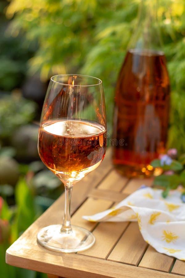 O vinho cor-de-rosa frio nos vidros serviu no terraço exterior em wi do jardim fotografia de stock royalty free