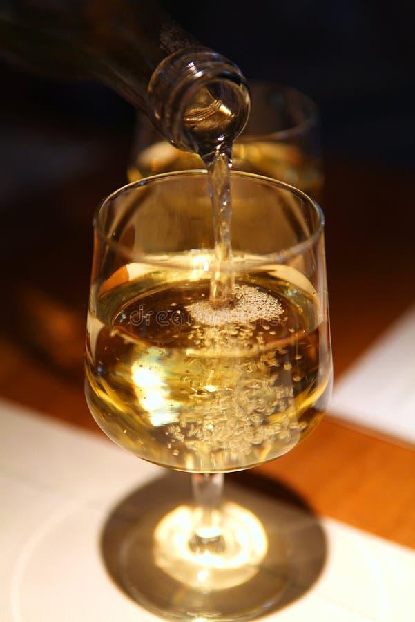 O vinho derrama da garrafa ao vidro imagens de stock royalty free