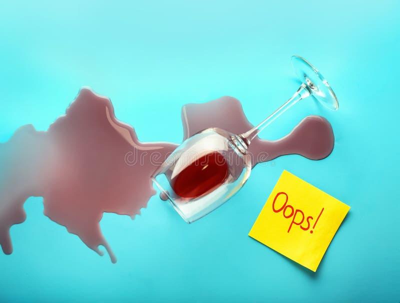 O vinho derramou o cartão virado do vidro e de papel com texto OOPS no fundo da cor Conceito do erro imagens de stock