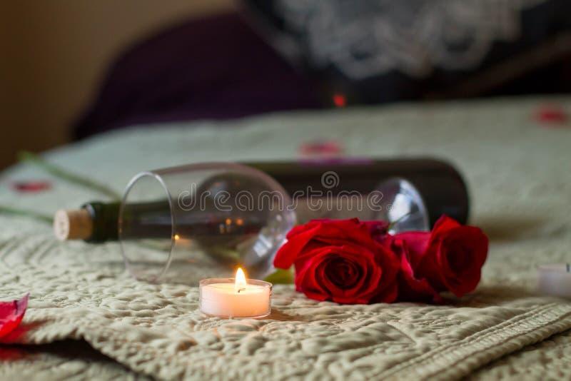 O vinho e as rosas do dia de Valentim na cama com chá iluminam-se foto de stock royalty free
