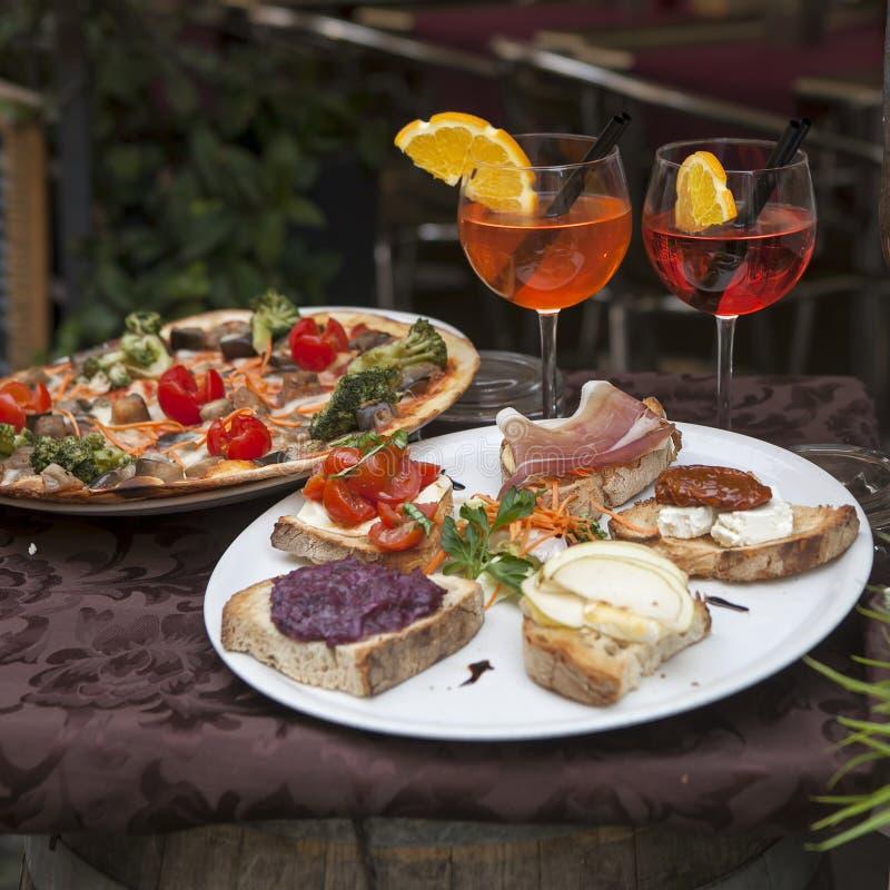 O vinho nos vidros, nas placas com pizza e sanduíches com jamon e no queijo na tabela na entrada ao restaurante fotografia de stock royalty free
