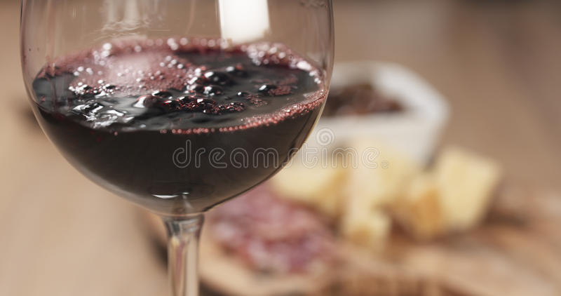 O vinho tinto derrama na frente dos aperitivos italianos dos antipasti imagens de stock royalty free