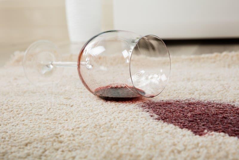 O vinho tinto derramou o vidro no tapete foto de stock