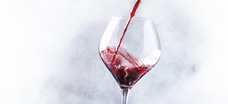 O vinho tinto seco francês, derrama no vidro, fundo cinzento, bandeira, foto de stock