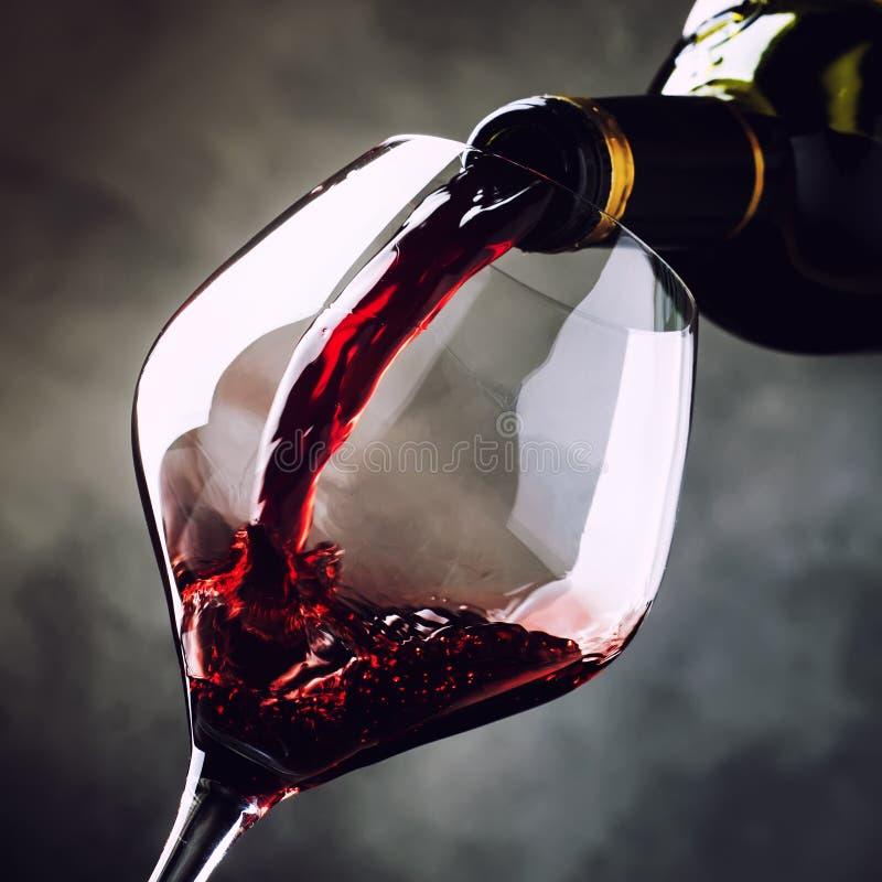 O vinho tinto seco francês, derrama no vidro, fundo cinzento, selectiv foto de stock royalty free