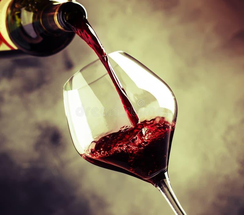 O vinho tinto seco francês, derrama no vidro, fundo cinzento, selectiv imagens de stock royalty free