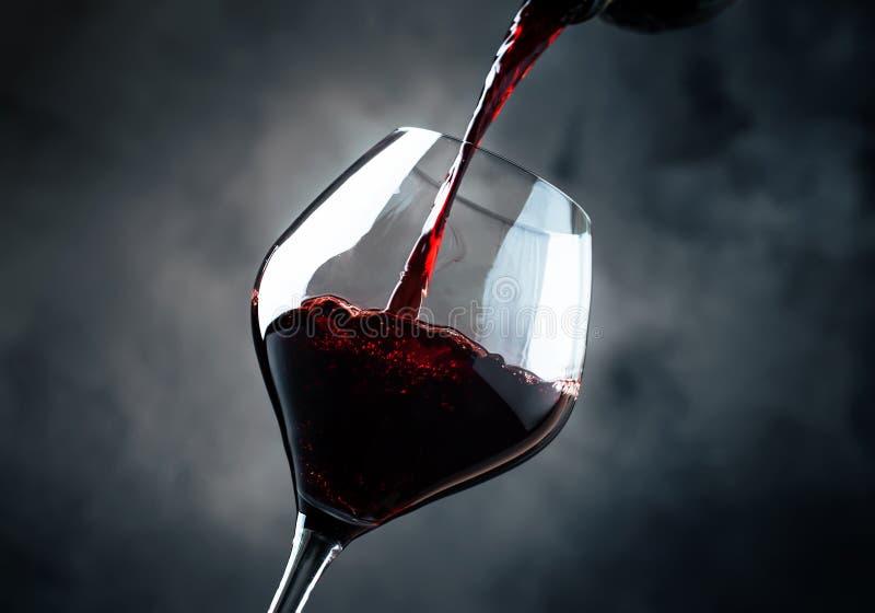O vinho tinto seco francês, derrama no vidro, fundo cinzento, selectiv imagens de stock