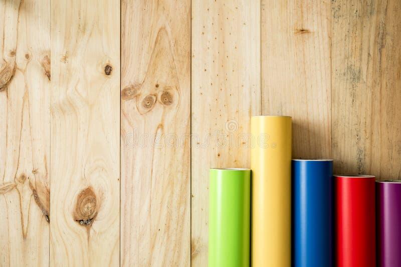 O vinil colorido rola no fundo de madeira imagens de stock royalty free