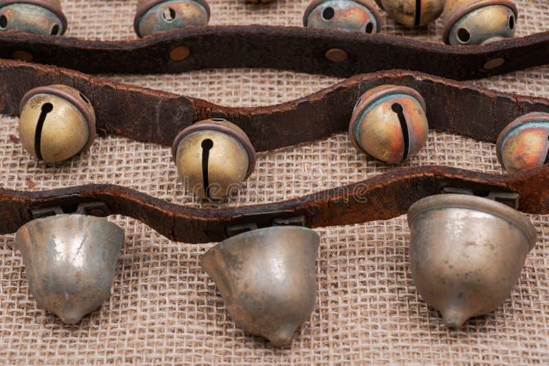 O vintage antigo oxida os sinos de trenó de bronze na correia de couro e na serapilheira fotografia de stock royalty free