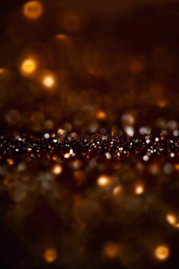 O vintage Defocused do brilho ilumina o fundo com ouro escuro e b imagens de stock
