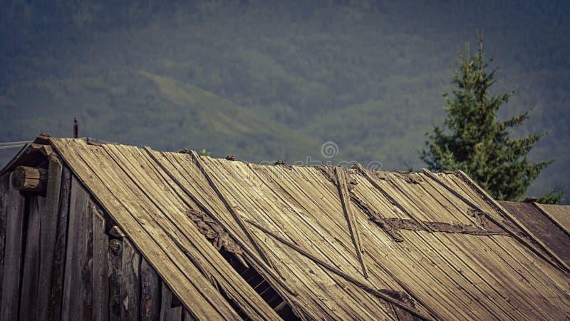 O vintage desvaneceu-se imagem de um telhado de madeira velho do celeiro que cai distante orvalho à falta da manutenção, uma expl fotografia de stock royalty free