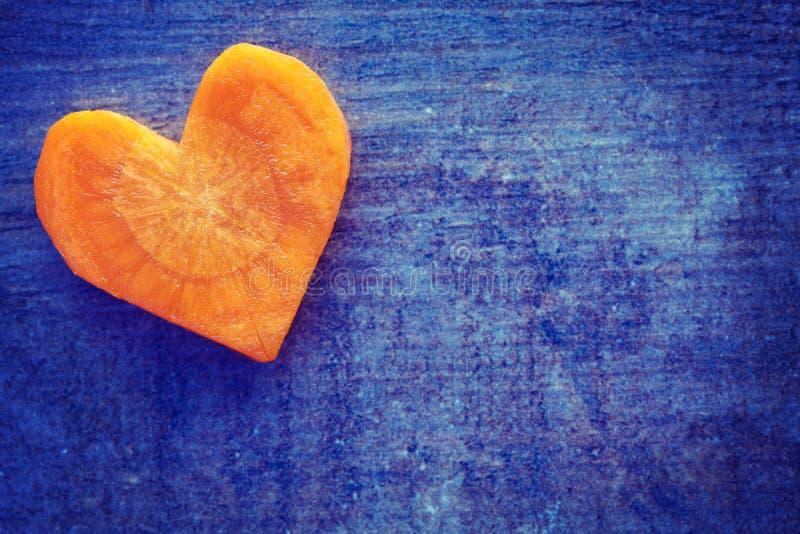 O vintage estilizou o coração feito da cenoura no fundo do grunge fotos de stock