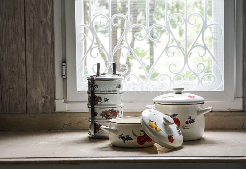 O vintage que cozinha o potenciômetro e o portador do tiffin ajustou-se na mesa de cozinha imagem de stock