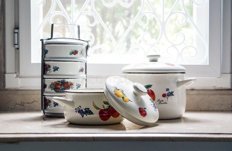 O vintage que cozinha o potenciômetro e o portador do tiffin ajustou-se na mesa de cozinha imagem de stock royalty free