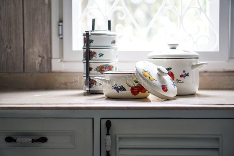 O vintage que cozinha o potenciômetro e o portador do tiffin ajustou-se na mesa de cozinha fotos de stock