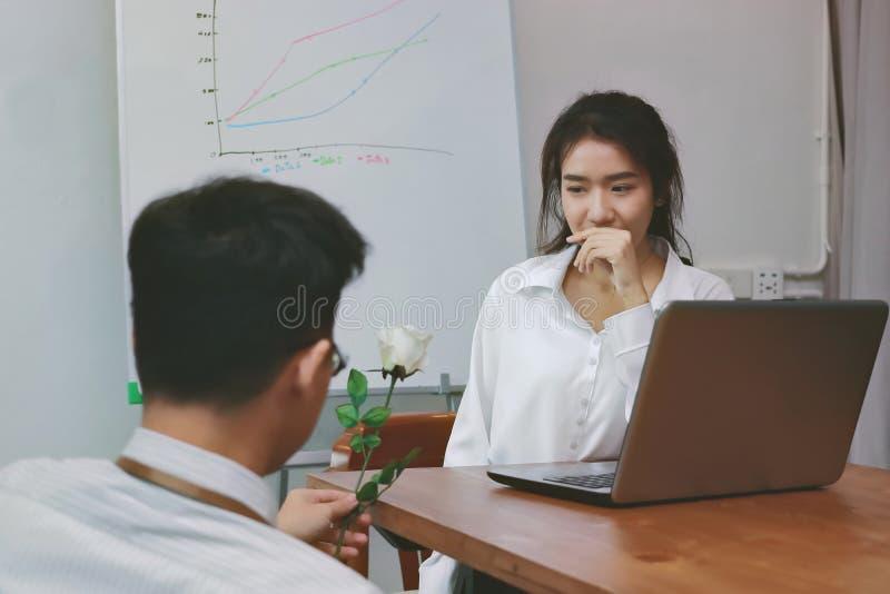 O vintage tonificou a imagem da mulher asiática nova atrativa entusiasmado para obter uma rosa branca no escritório no dia do ` s fotografia de stock