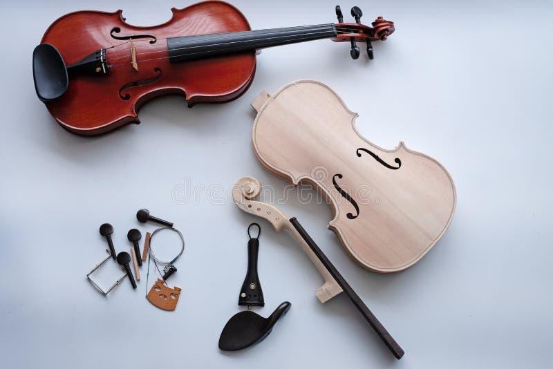 O violino cru posto ao lado do violino terminado imagens de stock