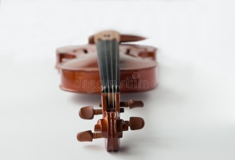 O violino que encontra-se horizontalmente com ajustamento cavilha perto do pelotão da frente no fundo branco imagens de stock
