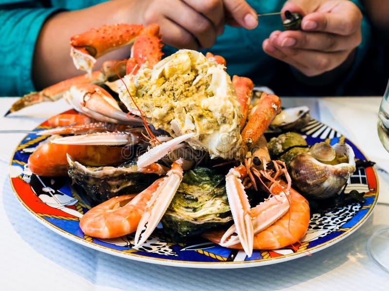 o visitante come o marisco no restaurante local dos peixes fotografia de stock