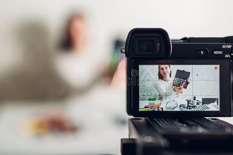 O vlogger da beleza da jovem mulher ou a gravação profissional do blogger compõem a câmera e o tripé de utilização tutoriais imagem de stock royalty free