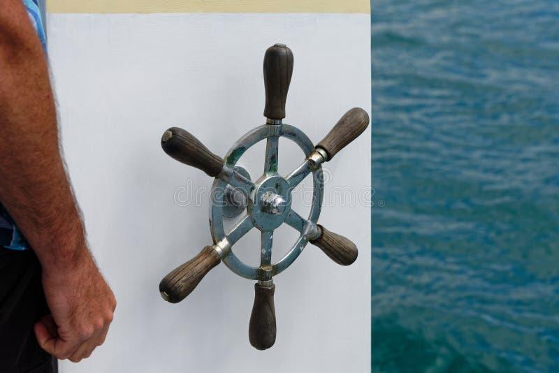 O volante de um navio contra um fundo branco com o mar à direita imagens de stock