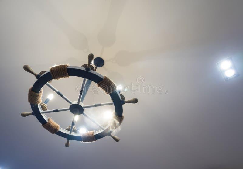 O volante do barco foi adaptado em uma lâmpada do teto fotografia de stock