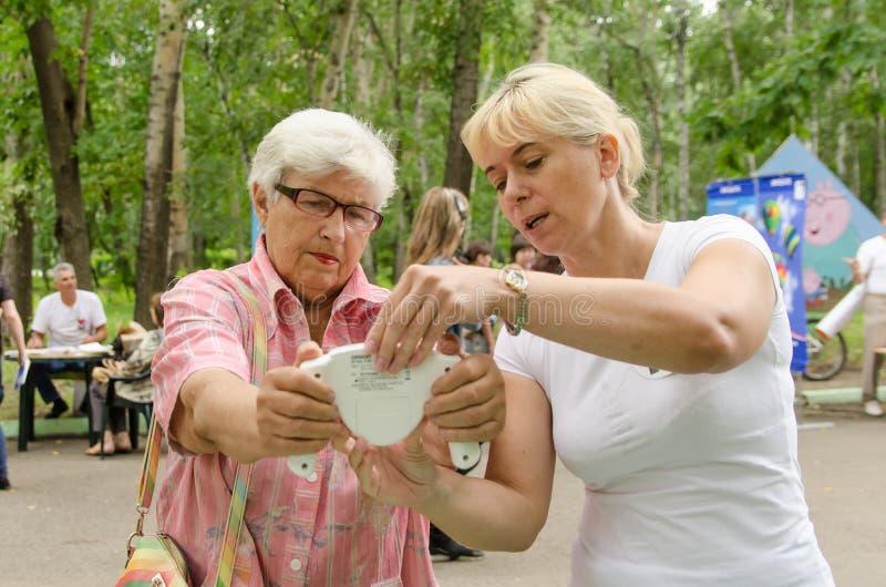 O voluntário fêmea mostra a mulher idosa como guardar corretamente a gordura corporal para monitorar em suas mãos fotografia de stock