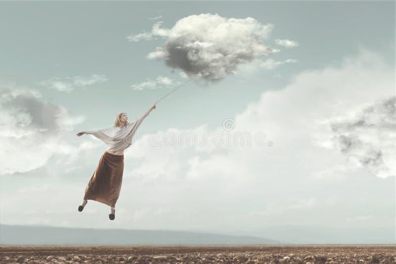 O voo da mulher no céu levou por uma nuvem imagem de stock