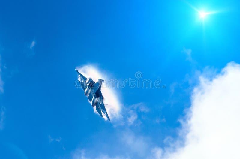 O voo do avião de combate da batalha mergulha quebrando nuvens em uma luz do sol do céu azul imagens de stock