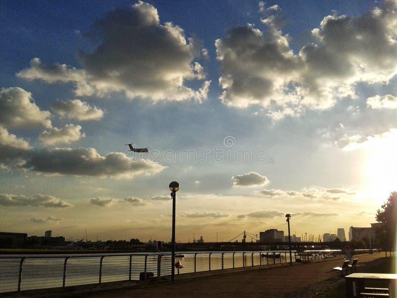 O voo do avião do aeroporto da cidade de Londres, Albert real entra o por do sol fotos de stock