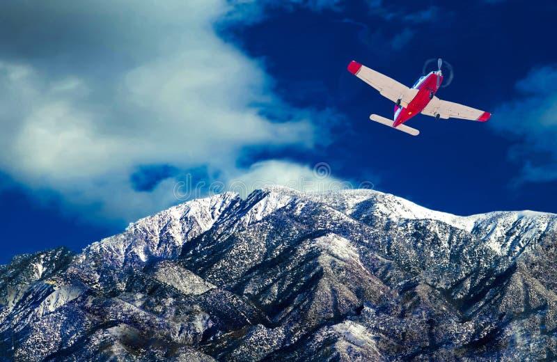 O voo dos aviões do único motor sobre a neve tampou a montanha imagens de stock