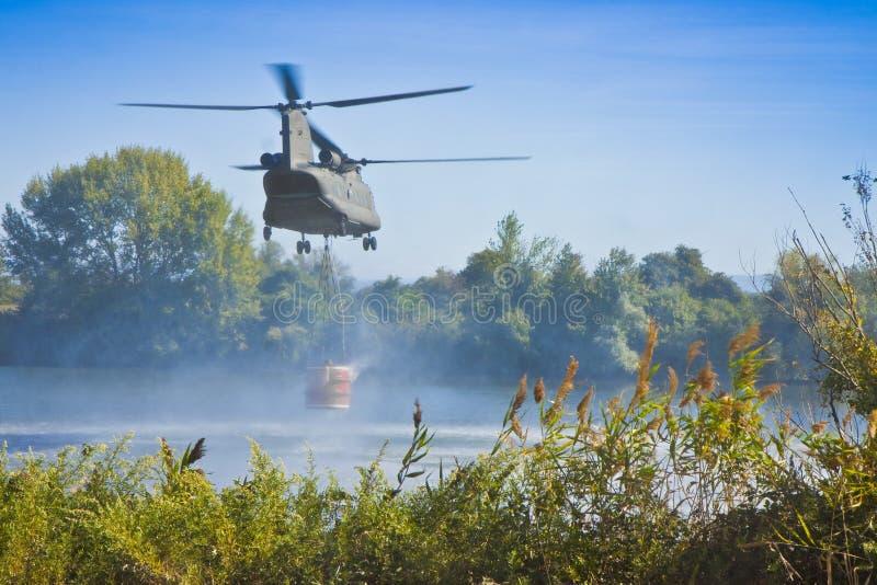 O voo italiano do helicóptero da luta contra o incêndio sobre um lago ao recolhe a água em uma cubeta para extinguir um fogo imagens de stock
