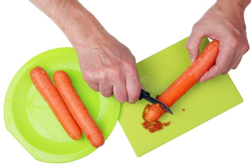 O vovô do cozinheiro chefe com uma faca e mãos descasca fora as cenouras cobre dentro foto de stock royalty free